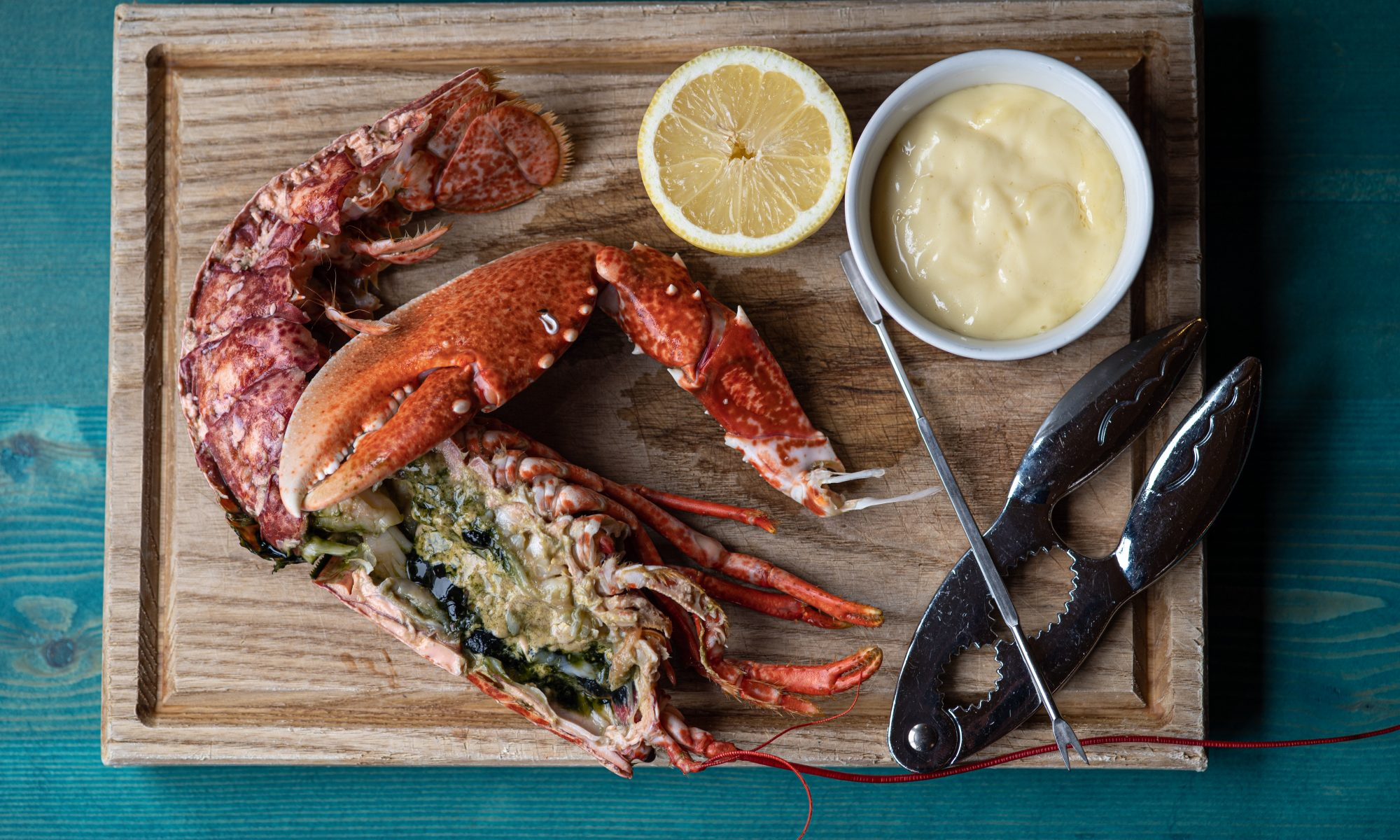 Half a stuffed Cornish lobster with lemon and dipping sauce