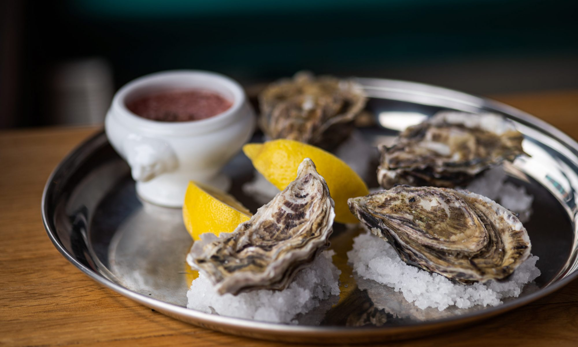 Rock Oysters on a white plate with slice of lemon and dipping sauce